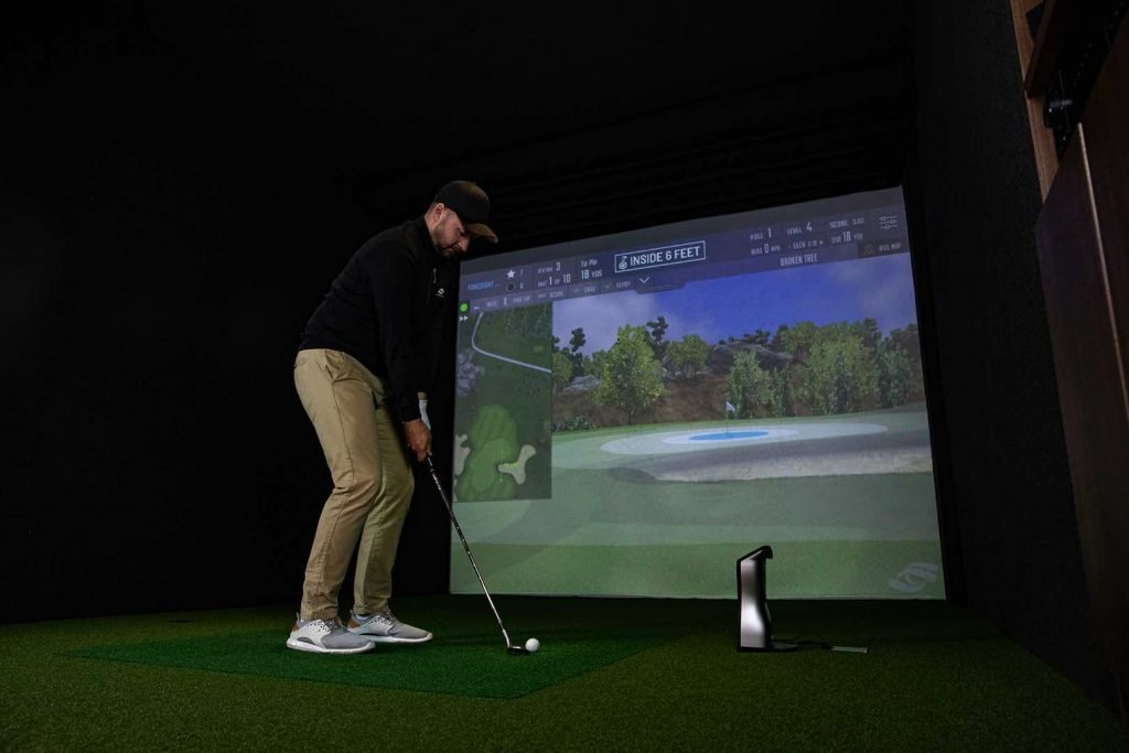 Golfer using an indoor projected golf simulator